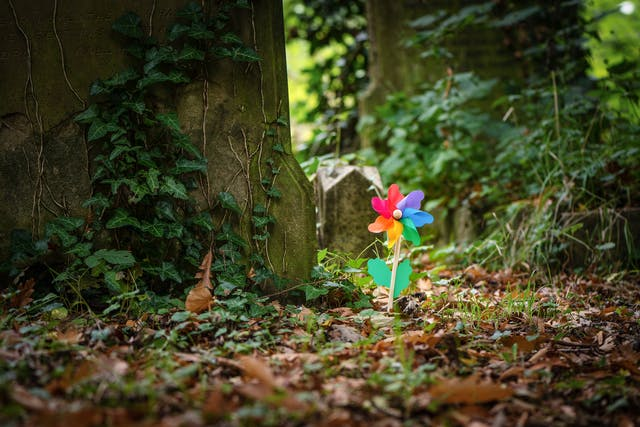 Photograph of a colourful windmill sitting within the surroundings of a cemetery, with grave stones and ivy.