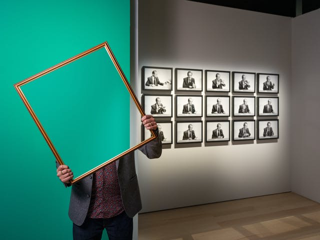 Photograph of a man in a gallery space holding a picture frame in front of his face and upper body. Within the picture frame you can see straight through him, as if his body and head have disappeared. In the background you can see a green painted wall and a grid of framed black and white photographs.