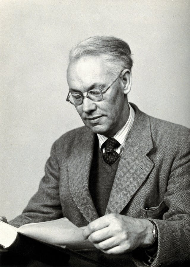 Black and white photograph of a middle-aged white man, Sir Christopher Howard Andrewes, wearing glasses and a tweed suit who is reading a book.