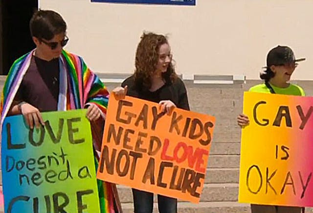 Teenagers hold signs saying