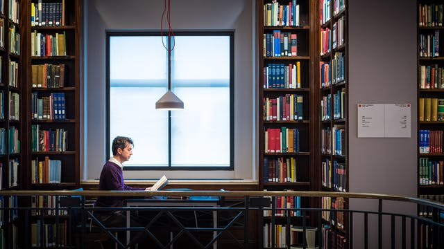 Photograph showing a man sat reading a book at a table in front of a window, surrounded by floor to ceiling  library shelves containing books.