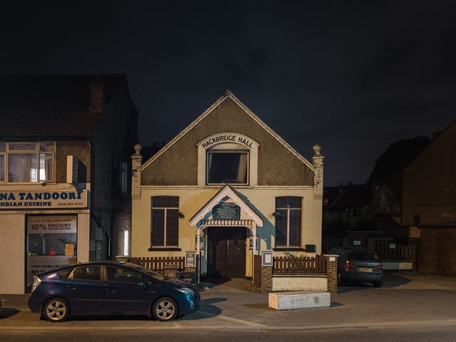 Photograph of Hackbridge Christian Spiritualist Church at night.  The double storey building is located in the centre of the frame, with a Indian cuisine restaurant to the left. of the building.  In the foreground is a blue sedan.