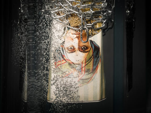 Photograph of a promotional poster for the 1920s mind reader, Alexander, hanging upside down in a tank of water wrapped in chains and padlocks, surrounded by bubbles.