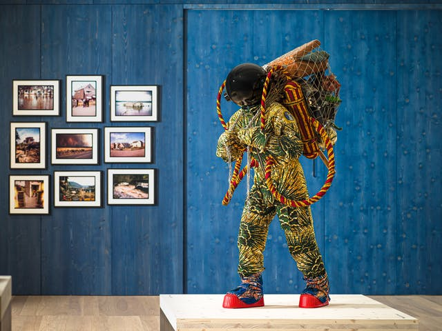 Photograph of an exhibition gallery space, with a blue stained wood wall in the background. In the foreground is a life-size artwork of a figure resembling an astronaut. carrying a large net containing assorted objects including a suitcase.