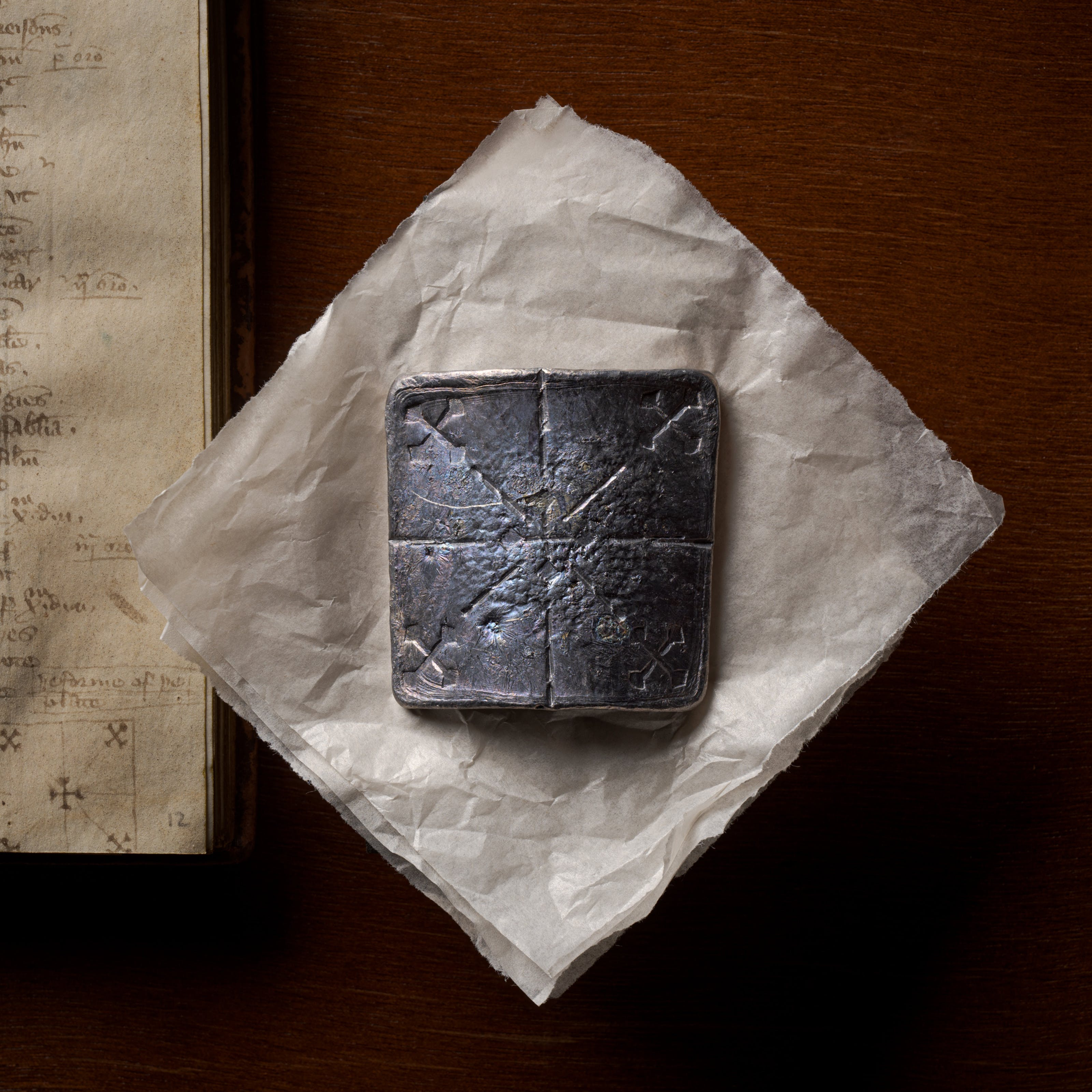 Photograph of a curved lead healing plate about ten centimetres square, sitting flat on a piece of conservation paper.  Below the lead plate, to the left, is the manuscript from which the original instructions to make the plate can be found.  The lead plate has been inscribed with 5 crosses; one diagonal cross in each corner with lines leading to a central, right-way-up, cross.