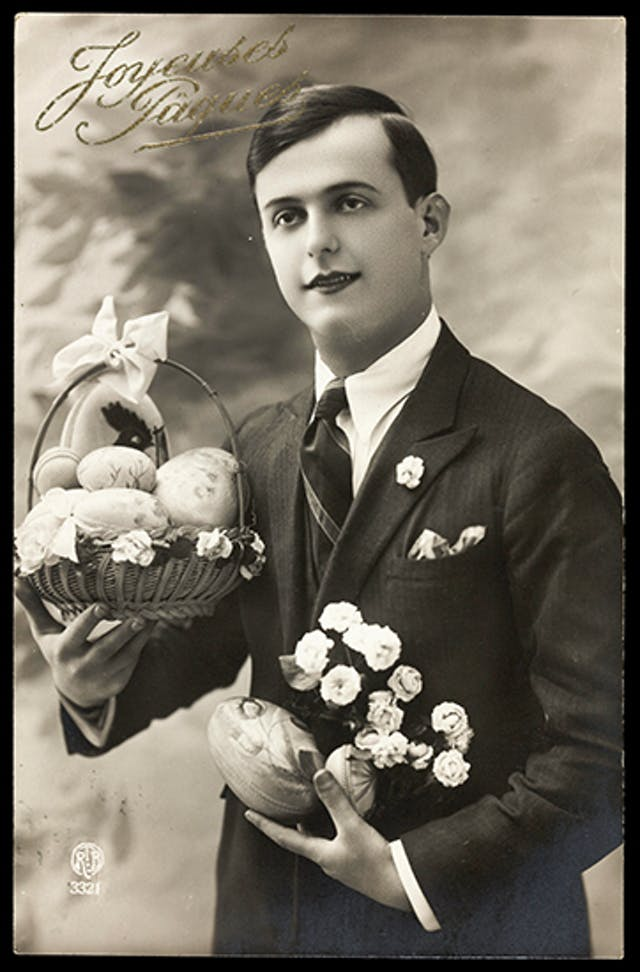 A young man in a smart suit with a basket of decorated Easter eggs in one hand and a single decorated egg and a bunch of flowers in the other hand.