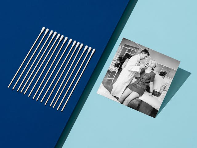 Photograph of clinical light blue background with a light blue surface floating above the dark blue and appearing from the left hand side, covering half the image. Propped up on the light blue surface is a black and white archive photograph showing a woman perched on the edge of a hospital bed whilst a male doctor administers an anti-flu vaccine up her nose. On the left hand side of the image is a row of neatly lined up medical swabs.