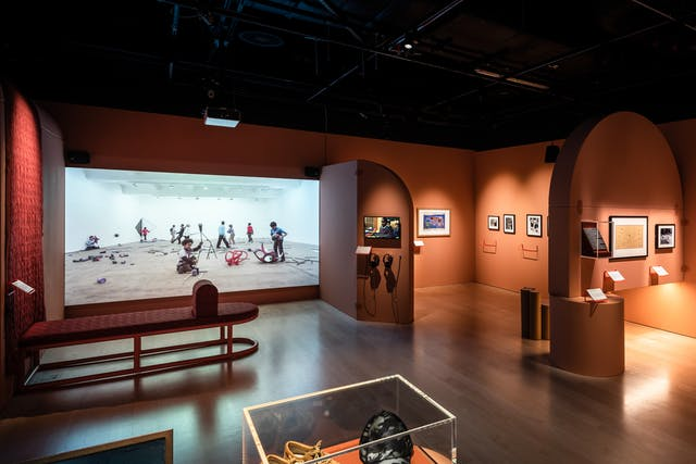 Photograph of an exhibition gallery space containing orange walls with arched details and framed wall mounted exhibits. To the right of the frame is a projected film. The current film still shows young boys in a large white space surrounded by fragments of what were larger sculptures.
