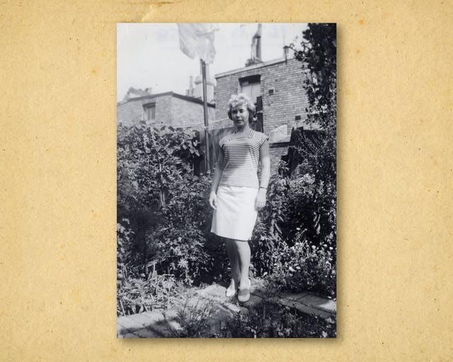 Photograph of a black and white photographic print, resting on a brown paper textured background. The print shows a woman in full length standing in the back garden of a row of houses. She is looking to camera, wearing a white skirt and stripped top. She is surrounded by shrubs and trees. Behind her are brick houses.