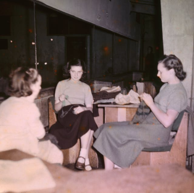 Photograph from the mid-20th Century Peckham Pioneer Centre, showing three women seated at a table, knitting. The building in which they sit has concrete columns and large windows.
