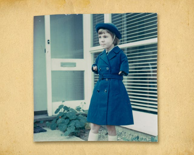 Photograph of a colour photographic print roughly cut around the edges, resting on a brown paper textured background. The print shows a small young girl in a long blue coat and matching blue hat. She is standing outside a house with a large front window and glass panelled front door which is open. On the ground are the leaves of a plant. The girl is looking off to the left. Her arms are short as a result of her mother being prescribed Thalidomide during her pregnancy.