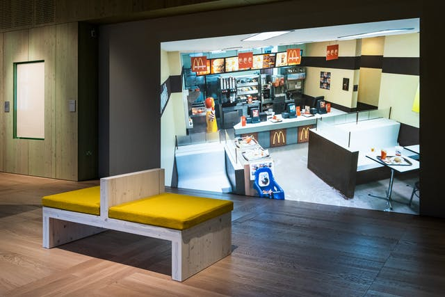 Photograph of a gallery installation showing a bench with yellow cushions facing a large video projection. The projection shows the inside of a McDonalds restaurant looking down from a high viewpoint in which the restaurant floor is beginning to flood with water.