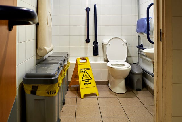 Photograph though the doorway of an accessible toilet showing part of the door and doorframe, along with the contents of the room, toilet, basin and sanitary bins. The room looks run down and dirty. To the left of the toilet is a yellow, caution wet floor sign.