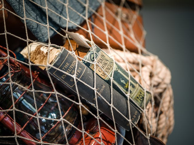 Photograph of a close-up detail of the net being carried by a life-size artwork of a figure resembling an astronaut. Within the net is a couple of books, one titled Captain Cook