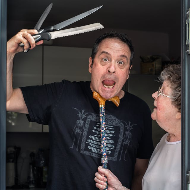 Photograph of a man standing in a glass patio doorway with his mother. The man is looking straight to camera with his mouth open, eyes wide and slightly mad look on his face. In his right hand held above his head are 3 kitchen knives held in a fan shape. His mother is standing to his left in profile, looking up at his face. In her right hand she is holding a walking stick, the handle of which she has tucked under his chin in a disciplinary fashion.