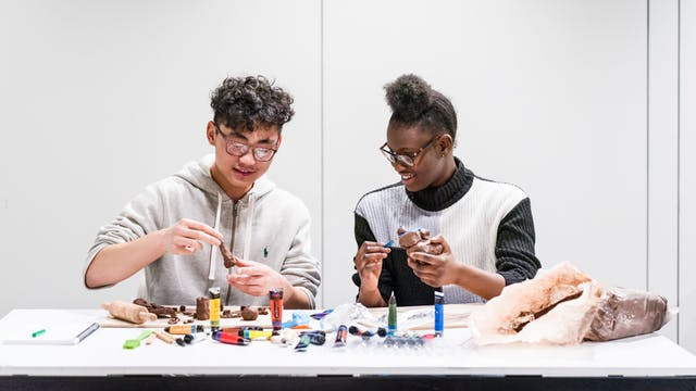 Photograph of a young man and woman sitting side by side, taking part in a table based workshop involving paints, clay and small sculptures.