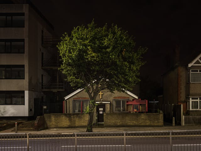 Photograph of Romford Christian Spiritualist Church at night. The single storey church has red and white features with a pitched roof.  The centre of the facade shows a gilded cross, with the facade itself being pebbledash and is partly hidden by a tree.  To the left of the church is a multi-storey commercial office, and to the right is a double storey post-war residential building.