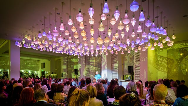 Photograph showing an audience listening to a spotlit speaker in the Wellcome Café, under colourful ceiling lights.