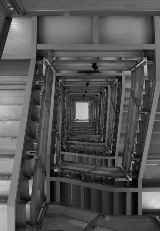 Photo shows the long distance to the ceiling when looking up from the bottom of a stairwell.