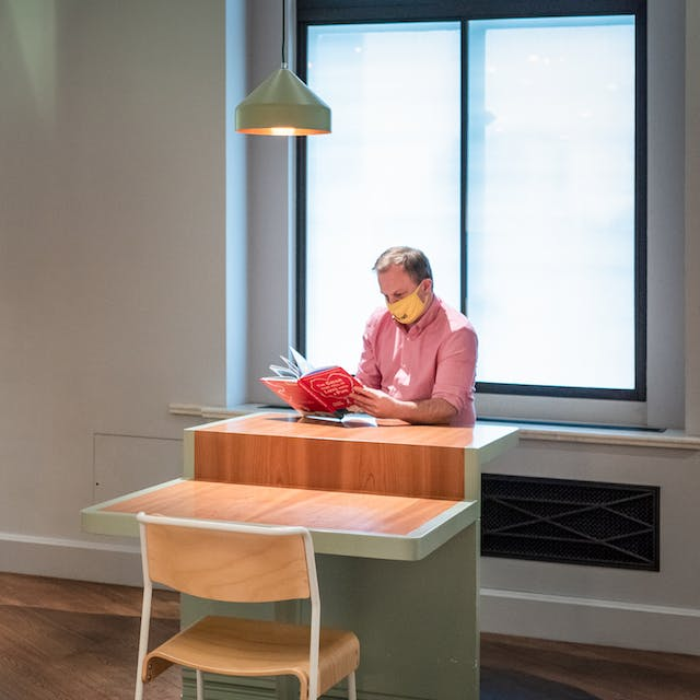 Photograph of a museum gallery space with free standing book shelves, wooden chairs and small table tops. Sat at the table on the right of the image is a man in a pink shirt wearing a yellow face covering. He is reading a book. Behind him is a large window with a diffused blind draw down. To the left of the image by the book case is a woman in a stripy jacket, also wearing a face covering. She is looking up at a the contents of a high shelf.