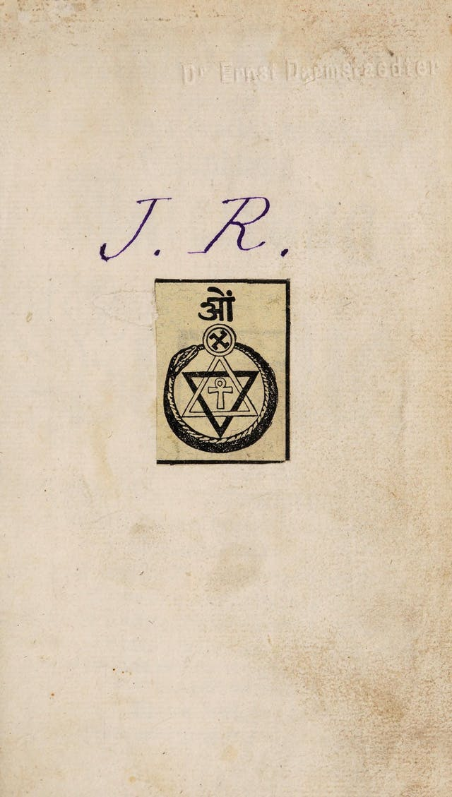 Bookplate on the centre of a page from a book.  The bookplate depicts a several mystic symbols and a snake eating its own tail.  Above the bookplate, the initials J.R. have been inscribed.