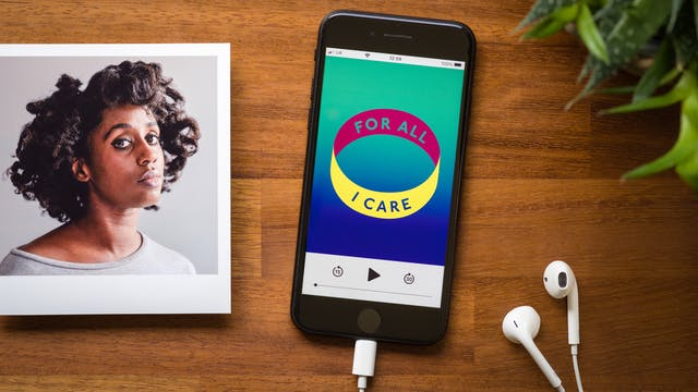 Photograph of a smartphone on a wooden tabletop. Plugged into the phone is a pair of white earbud headphones. On the screen of the phone is a podcast screen with a graphic identity of a coloured ring with the words