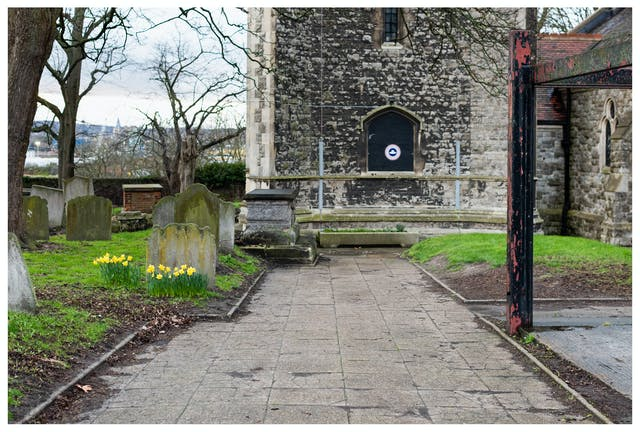 Photograph of a churchyard with the church buildings and leafless trees in the background. In the foreground there are a number of gravestones and grassed areas. To the centre left is small crop of bright yellow daffodils.