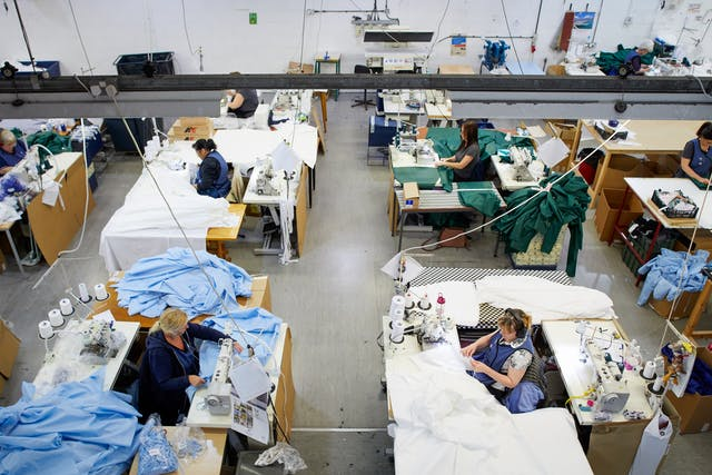 Photograph of a series of workstations within a clothing manufacturing workshop. The viewpoint is from a high walkway which looks down on the workstations. At each workstation is a woman working at a sewing machine, surrounded by white, green and light blue fabric.