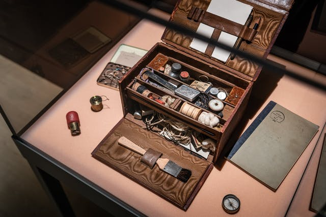 Photograph of an open wooden box containing lots of small items, in a display case as part of the Smoke and Mirrors exhibition at Wellcome Collection.