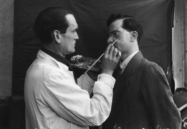 Captain Francis Derwent Wood holds an artist