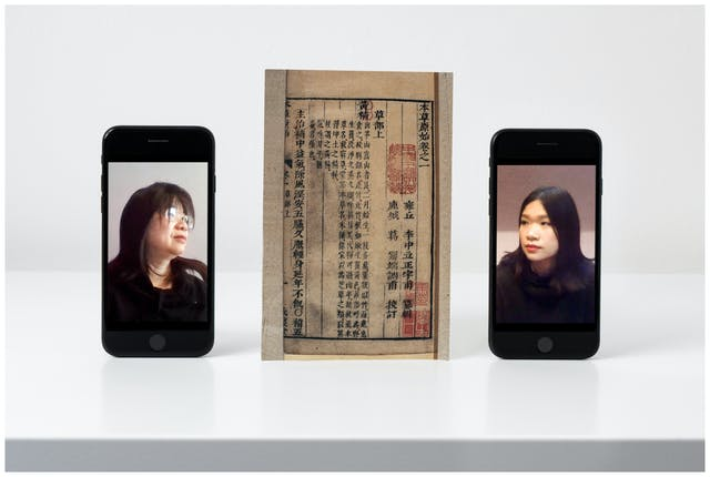 Photograph of a white, slightly glossy self against a white wall. On the shelf standing upright are two smartphones. On the screen on the left hand phone is a portrait of an older woman dressed in black looking to the right. On the screen on the right hand phone is a portrait of a younger woman dressed in black looking to the left. Between the two phones is a print from a Chinese medicinal book.