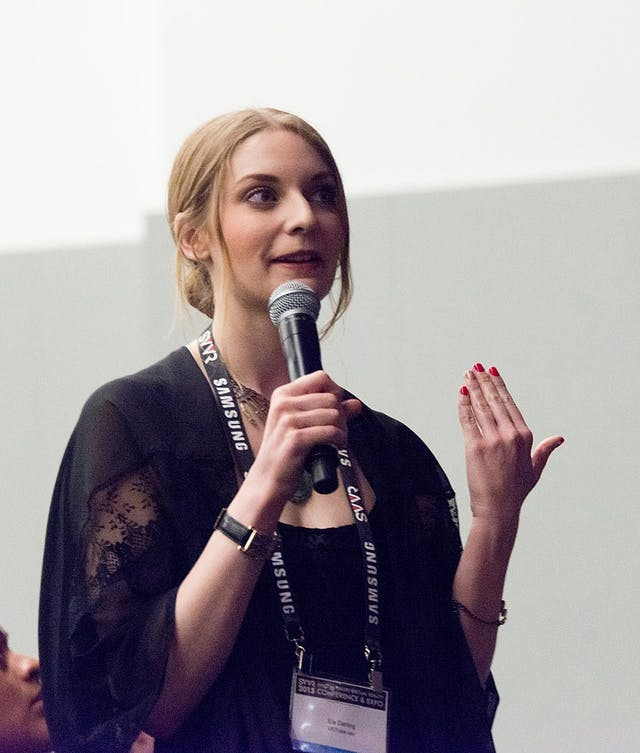 Colour photograph of Ela Darling holding a microphone and asking a question whilst wearing a conference lanyard.