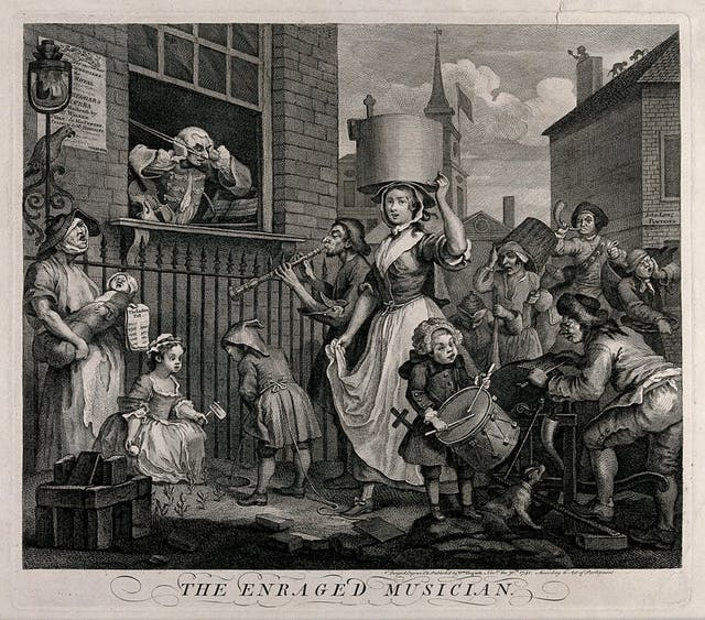 Black and white etching showing a man at a window wearing a wig holding a violin bow and with his hands covering his ears. In the street scene in front of this window, a woman appears to be singing and holding a crying baby; a child spins a rattle and another urinates against wall; a man plays a flute; a boy beats a drum; a person pedals a device whilst a dog barks at his feet; a man blows a horn; and another clutches the side of his face and appears to be moaning aloud. In the distance, cats fight on a rooftop and a sweep emerges from a chimney and appears to be waving.
