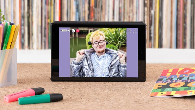 """Photograph of a tablet standing on a wooden surface with a vinyl record shelf behind containing the spines of many colourful records. On the tabletop are coloured highlighter pens, a pen pot containing pens and an open magazine showing colourful graphics. A photographic portrait of Jamie Hale is on the tablet screen with video call icons """"People"""", """"Chat"""" and a red telephone icon."""