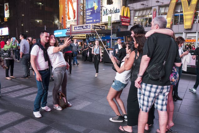Colour photograph of two groups facing one another whilst taking selfies. On the left a man smiles and a woman pouts whilst leaning backwards to fit into the picture, on the right a woman holds a selfie-stick and leans back towards another two men and two women.