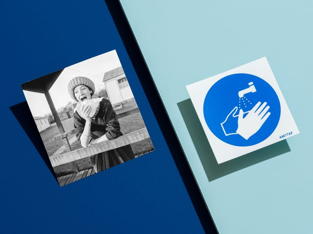 Photograph of clinical dark blue background with a light blue surface floating above the dark blue and appearing from the right hand side, covering half the image. Propped up on the dark blue surface is a black and white archive photograph showing a woman outside in a wooly hat leaning against a wooden handrail of a walkway, pretending to sneeze into a handkerchief. Floating on the right hand side of the image is a blue and white graphic safety notice showing a flowing tap and washing hands.