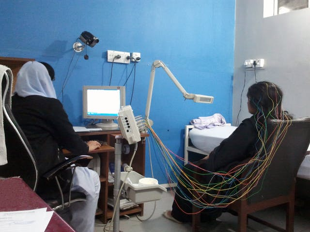 A woman seated with her back to the camera with wires in her hair having an EEG asa nurse watches a monitor next to her.