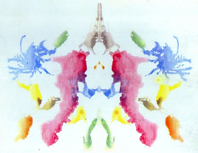 A yellow, pink, green and blue symmetrical inkblot.