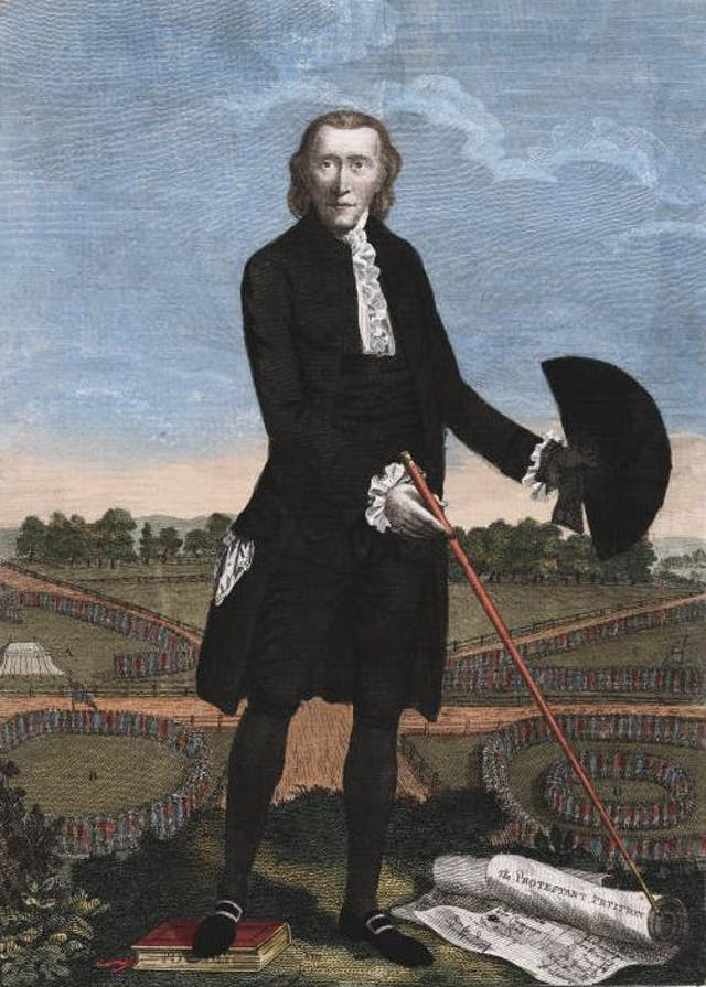 "Satirical print depicting Lord George Gordon.  Gordon stands full face, pointing with his cane to a roll inscribed ""Protestant Petition"", which shows signatures in two columns, another roll lies beside it. His right foot rests on a book inscribed ""Popery"". He is plainly dressed, lank hair falling on his neck; in his left hand, which is gloved, he holds out his hat and his other glove. Behind him is the point of intersection of the five roads which crossed in St. George"