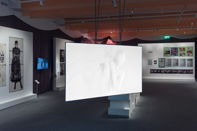 Photograph of the Misbehaving Bodies exhibition at Wellcome Collection, showing a wide view of the space. In the foreground is a video piece by Oreet Ashrey titled