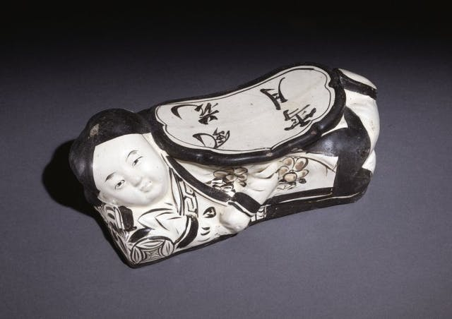Colour photograph of a black and white ceramic pillow in the shape of a woman reclining.