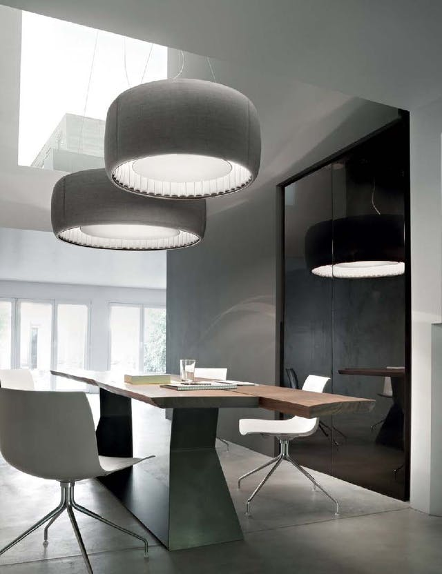 Colour photograph of a room with table and chairs below large round grey light fixtures, which are Silenzio lights by Luceplan.