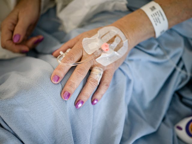 Photograph of the hands of a patient with glittery purple painted fingernails, resting on a light blue hospital bedsheet. The patient