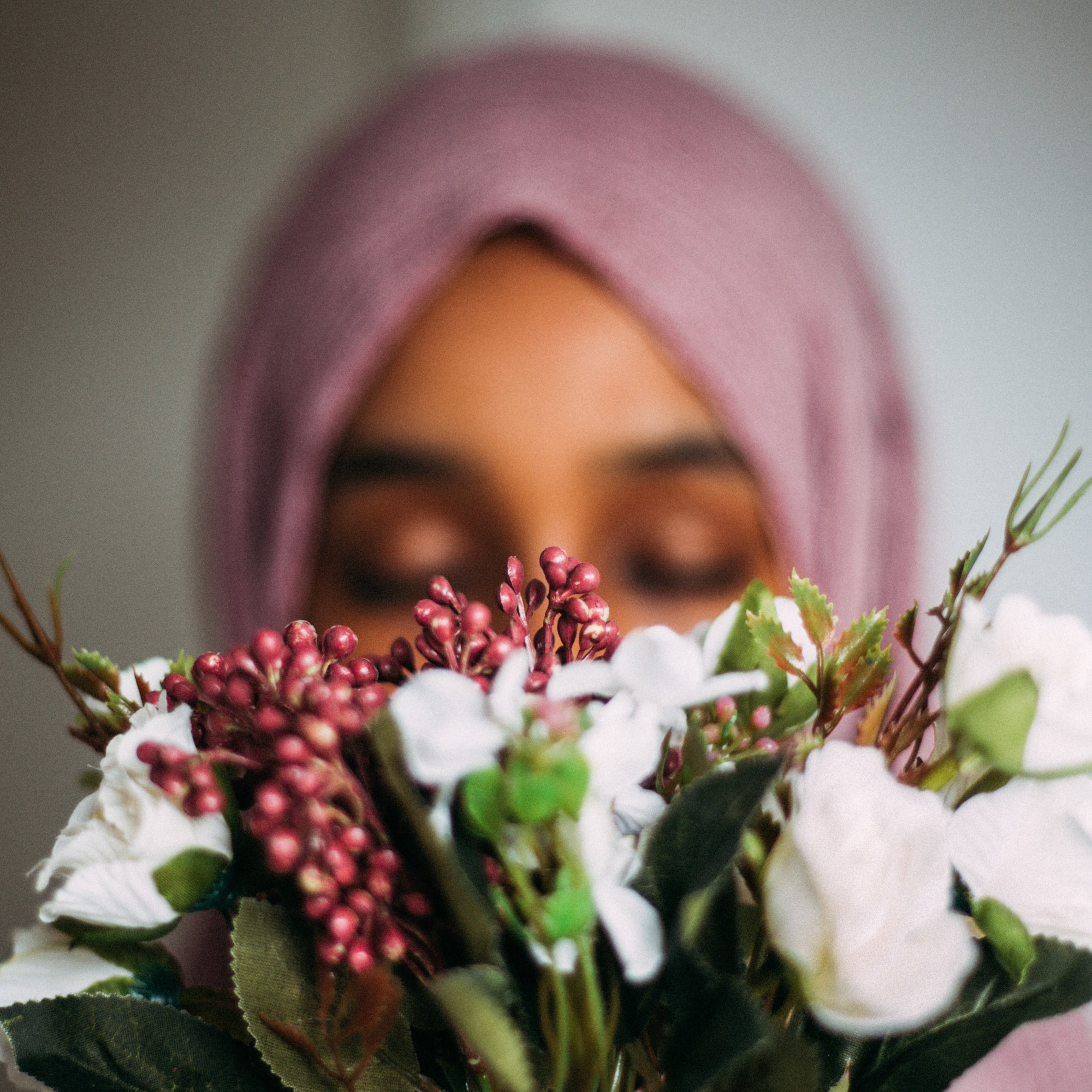 Photograph of a woman wearing a pink head scarf facing towards the camera. Her face is out of focus and partially obscured by a bunch of flowers.