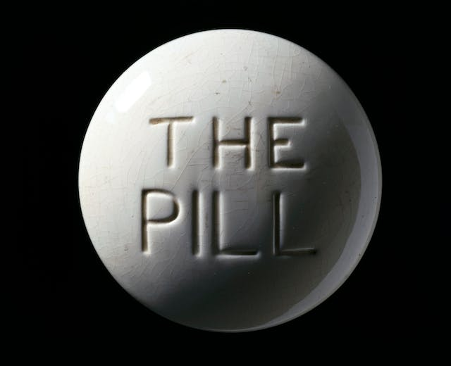 "Photograph of a contraceptive pill model, Europe, c. 1970. White crackled glaze, with debossed ""THE PILL"" text in centre, on a black background."