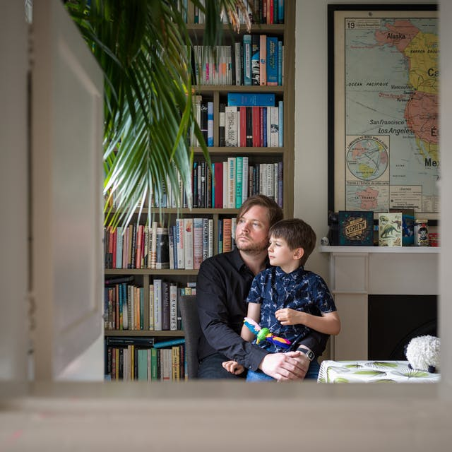 Photograph of a man sitting in a dining room with his arms around his son, sitting on his lap. Behind them is a bookcase and part of a world map. They are framed by the opening of a hatchway in the wall.