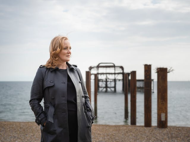 Photograph of a blonde woman as she gazes to the right of the frame on a sea front.  Out of focus behind her is a pebble beach with a burnt out pier.