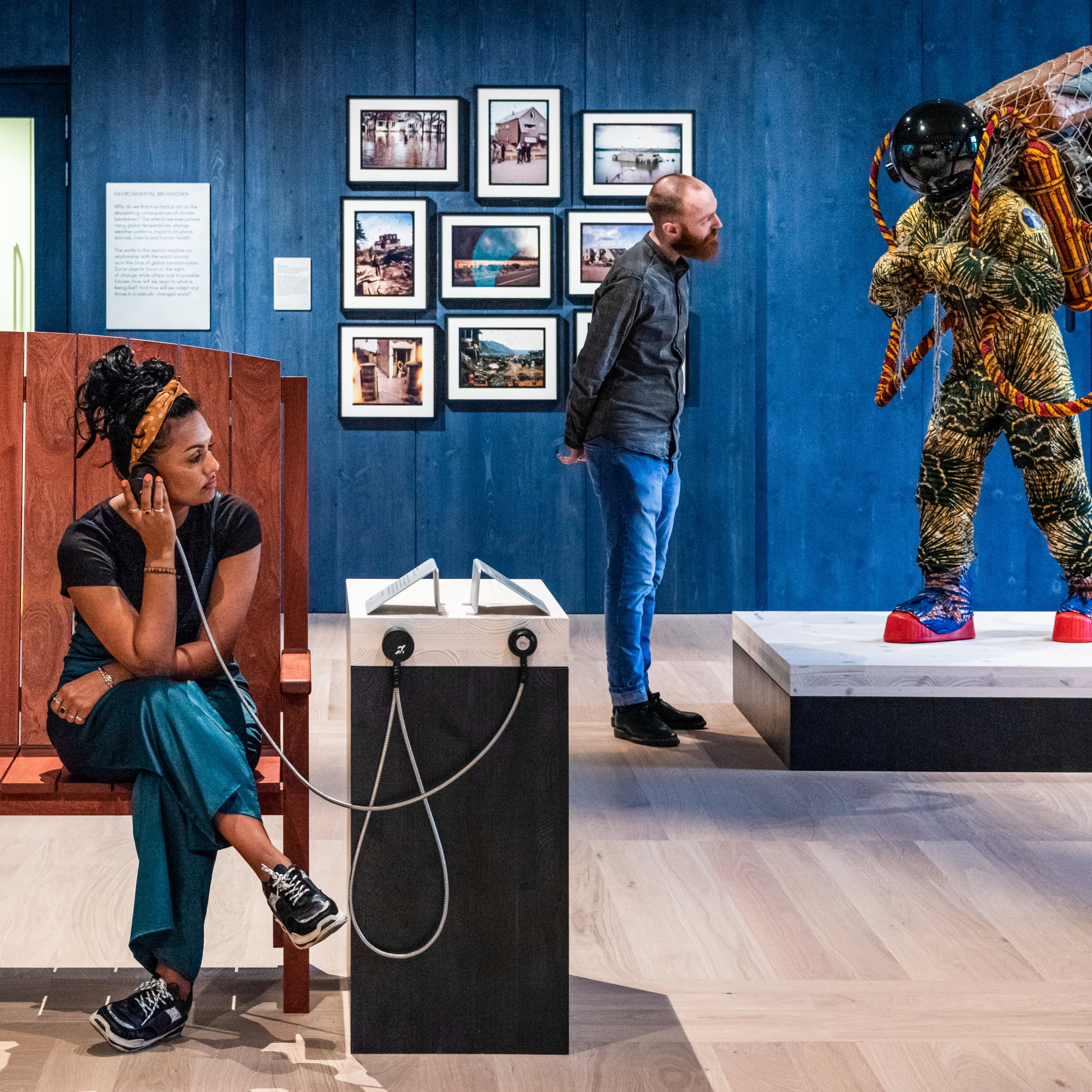 Photograph of an exhibition gallery space, with a blue stained wood wall in the background, in front of which a young man looks at a life-size artwork of a figure resembling an astronaut. In the foreground a young woman sits on a wooden bench holding an audio speaker to her ear.