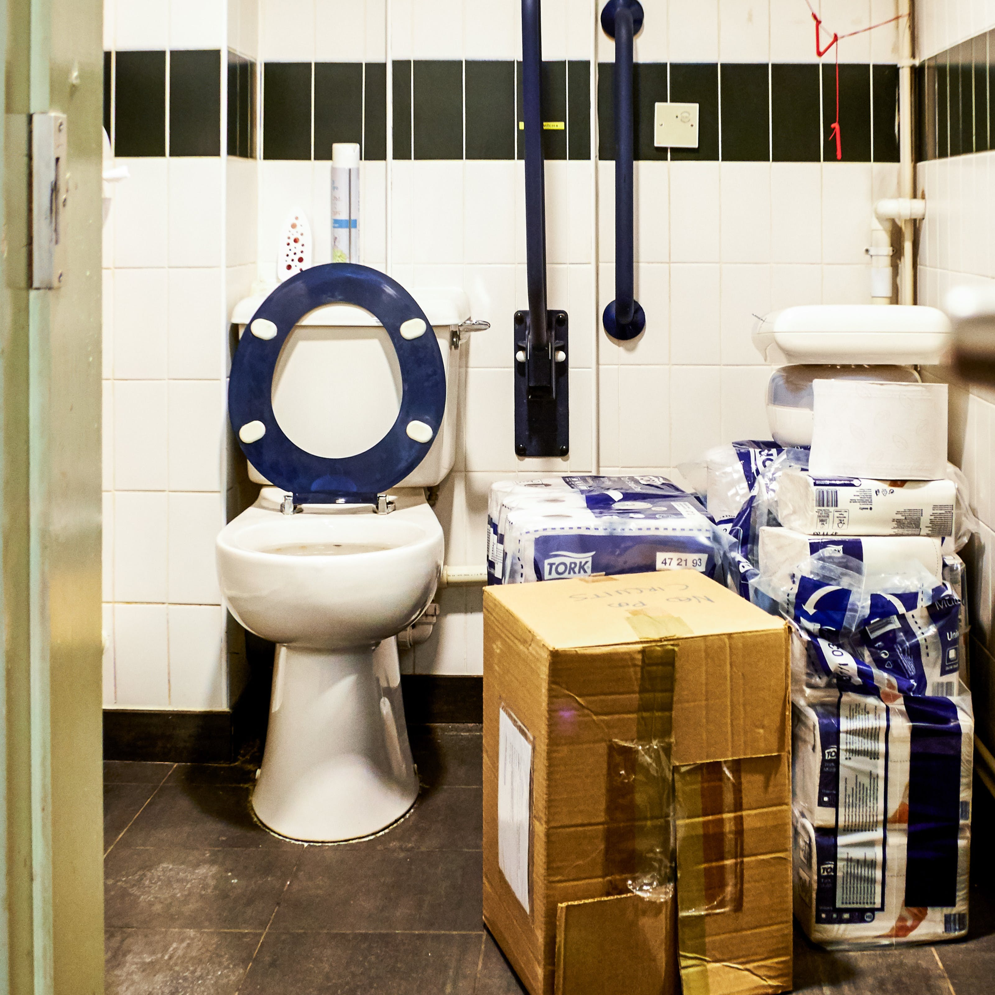 Photograph though a doorway into an accessible toilet. The floorspace next to the toilet is covered with a cardboard box and piles of packets of toilet paper.