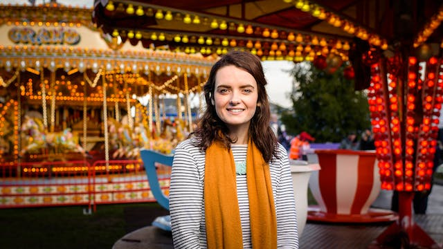 Photographic portrait of Emma Purce at a colourfully lit fairground.